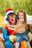 Little girl hugging a cheerful clown. Stock Photos