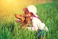 Little girl hugging dog,. Best friends. Happy little girl hugging dog, sitting on the grass Royalty Free Stock Photography