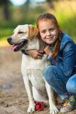 Little girl hugging a dog during a walk. Love. stock images