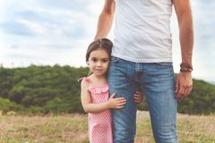 Little girl hugging father, summer day. Pretty smiling little girl hugging father`s leg. Summer happy family day in forest royalty free stock image