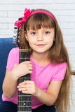 Little girl hugging a guitar Stock Photo