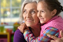 Little girl hugging her grandmother. Portrait of pretty little girl hugging her grandmother Royalty Free Stock Photos