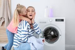 Little girl hugging her mother while she doing laundry. At home royalty free stock image