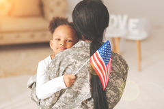Little girl hugging her mother and holding a flag. Sweet moment. Charming little girl hugging her mother in a military uniform, holding an American flag and royalty free stock photos