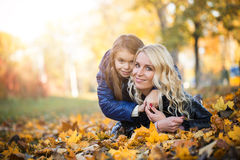 Little girl hugging her mother lying park Royalty Free Stock Image