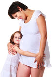 Little girl hugging her pregnant mother Stock Photography
