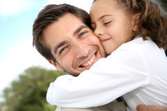 Little girl hugging her smiling father Stock Photos