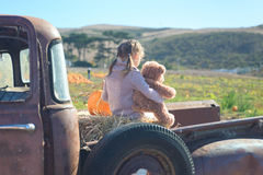 Little girl hugging her teddy bear sitting in the old truck at t Royalty Free Stock Photo