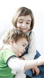 Little girl hugging her upset brother Stock Images