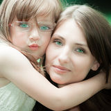 Little girl hugging his mother expressing tender feelings. Love. Royalty Free Stock Photos