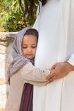 Little girl hugging Jesus. Biblical scene when Jesus says, let the little children come to me, blessing a little girl. Historical reenactment at an old water Stock Photos