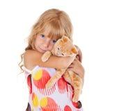 Little girl hugging kitten Stock Image