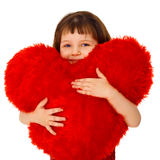 Little girl hugging a large toy heart Royalty Free Stock Images