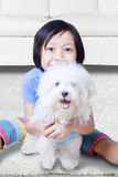 Little girl hugging a maltese dog Stock Photography