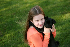 Little girl hugging puppy. Cute little girl holding black pug puppy Stock Photos
