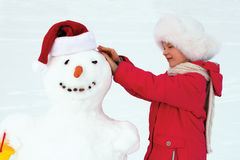 Little girl hugging a snowman and laughs. Winter fun Royalty Free Stock Photos