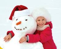 Little girl hugging a snowman and laughs. Winter fun Stock Photography