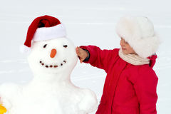 Little girl hugging a snowman and laughs. Winter fun Stock Photos