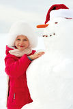 Little girl hugging a snowman and laughs. Winter fun Stock Images