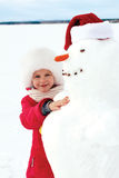 Little girl hugging a snowman and laughs. Winter fun Royalty Free Stock Image