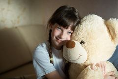 Little girl hugging teddy bear indoor in her room, devotion concept, big bear toy.  royalty free stock photos