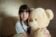 Little girl hugging teddy bear indoor in her room, devotion concept, big bear toy.  stock photography
