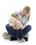 Little girl hugging teddy bear with mum Stock Photos