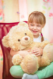 Little girl hugging Teddy bear. Little girl sitting on a chair with a Teddy bear Royalty Free Stock Image