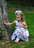 Child Outdoors With Her Doll stock photo