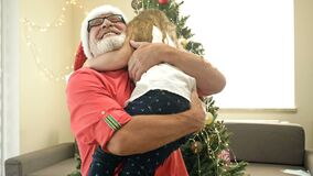 Little girl hugs her grandfather in Santa Hat. Against the background of the Christmas tree.