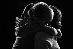 Little girl hugs her mother. Black and white image of a little girl hugging her mother Royalty Free Stock Photos