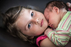 Little girl hugs her newborn sleeping sister Foto de archivo