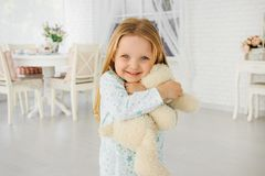 Little girl hugs a teddy bear. Smiles, emotions of happiness. Little girl playing with teddy bear royalty free stock images