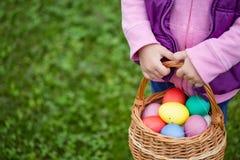 Little girl hunts Easter egg. Kids searching eggs in the garden. stock photos