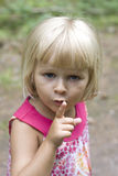 A little girl hushing. A 3 year old little girl holding up her finger for silence Royalty Free Stock Images