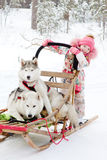 Little girl and Huskies in winter forest Stock Images