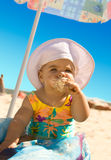 Little Girl with ice cream. The little girl on the beach under an umbrella with ice cream stock image