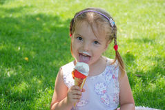 Little girl and ice-cream. Pretty girl eating ice cream on a hot summer day Stock Images