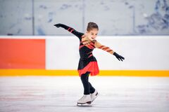 Free Little Girl Ice Skater In Beautiful Black Red Dress Ice Skating Of An Indoor Ice Arena Stock Photography - 196438002