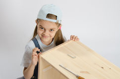 Little girl in image collector of furniture turn screw Stock Image