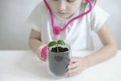 Little girl imagining herself as doctor while playing with pink stethoscope. Young plants. Caring for a new life. Climate change royalty free stock photos