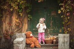 Free Little Girl In A Jacket And With A Pink Bow Stands On The Steps Of The Old Porch. Around Autumn Leaves, On The Steps Lies A Large Royalty Free Stock Photo - 184574975