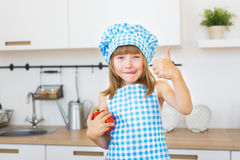 Little Girl In Cook Clothes Cuts A Bell Pepper On A Board