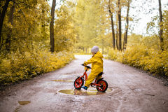 Little Girl In Yellow Waterproof Clothes With Bike Near A Puddle Royalty Free Stock Image