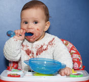 The little girl independently eats with a spoon Royalty Free Stock Photo