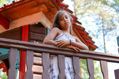 Little girl Indian leaned on the fence and looking down stock image
