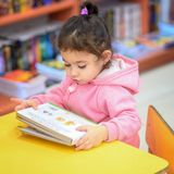Little Girl Indoors In Front Of Books. Cute Young Toddler Sitting On A Chair Near Table and Reading Book. Library, Shop. stock images