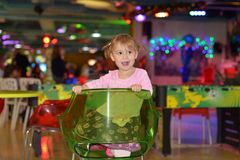 A little girl indulges in a chair in a children`s entertainment center. stock photos