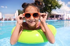 Little girl with inflatable ring in pool royalty free stock images