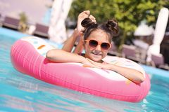 Little girl with inflatable ring in pool stock images